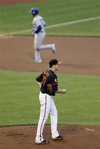 Baltimore Orioles starting pitcher Chris Tillman, bottom, walks up the pitching mound as Toronto Blue Jays' J.P. Arencibia rounds the bases after hitting a two-run home run in the second inning of a baseball game, Friday, July 12, 2013, in Baltimore. (AP Photo/Patrick Semansky)