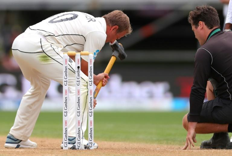 New Zealand's Neil Wagner (L) uses a groundsman's hammer on the pitch during day three of the second Test against England