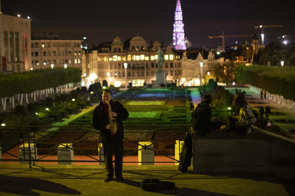 A street musician plays a saxophone at Mont des Art square during an autumn evening prior to the curfew in Brussels, Friday, Oct. 23, 2020. (AP Photo/Francisco Seco)