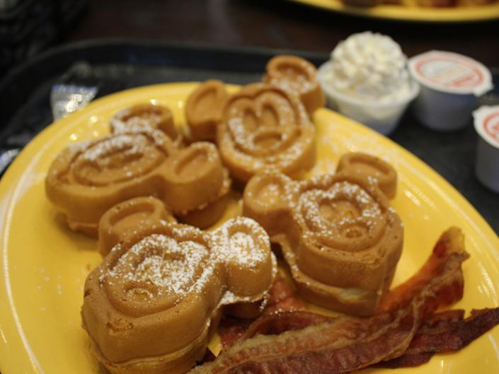Mickey-shaped waffles on a yellow plate with bacon taken at a Disney park breakfast.