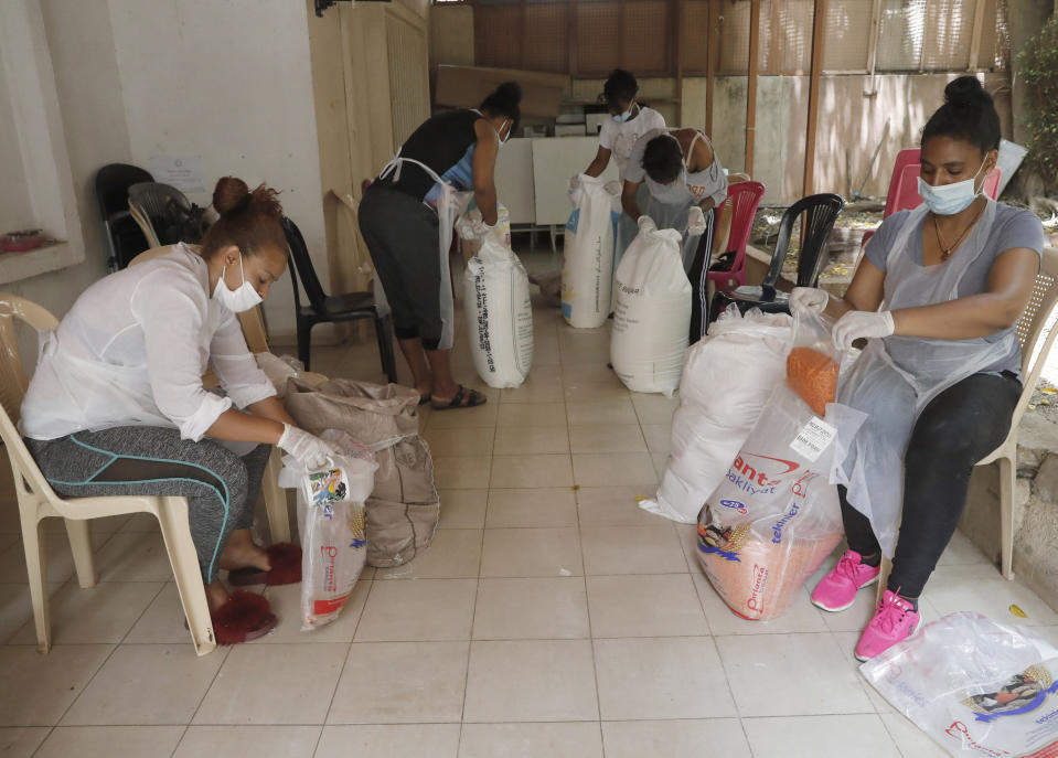"""In this Saturday, May 23, 2020 photo, Ethiopian workers pack food at the office of Egna Legna, meaning """"from us migrants to us migrants"""" in Amharic, Ethiopia's official language, which offers food packages for some who lost their jobs and helps others pay rent, in Beirut, Lebanon. Some 250,000 registered migrant laborers in Lebanon — maids, garbage collectors, farm hands and construction workers — are growing more desperate as a crippling economic and financial crisis sets in, coupled with coronavirus restrictions. With no functioning airports and exorbitant costs of repatriation flights, many are trapped, unable to go home. (AP Photo/Hussein Malla)"""