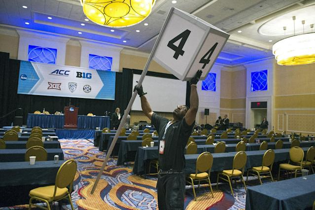 Audiovisual Technician Patrick Mack, Sr. starts to breakdown the NCAA's Autonomy Business Session's signage at the conclusion of the meeting, during the final day of NCAA Convention in Oxon Hill, Md., Saturday, Jan. 17, 2015. The five most powerful and wealthiest conferences in college sports passed NCAA legislation that increases the value of an athletic scholarship by several thousand dollars to cover the federally determined actual cost of attendance. (AP Photo/Cliff Owen)