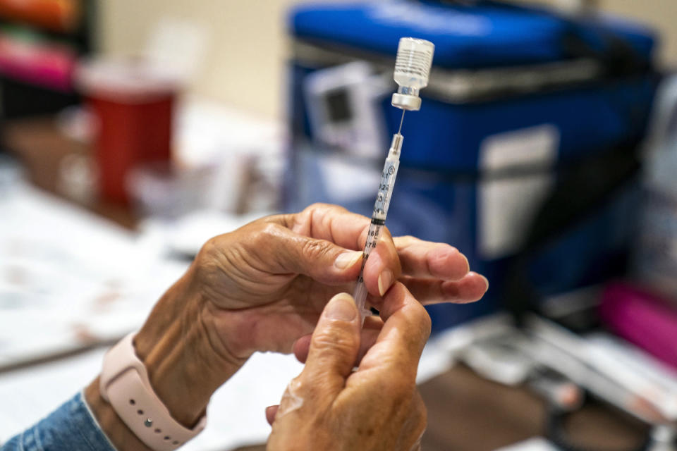 FILE - In this Sept. 14, 2021, file photo, vaccine provider prepares a dose of the COVID-19 vaccine at a clinic run by the Allegheny County Health Department at Casa San Jose, a non-profit serving Latino immigrants in the Beechview neighborhood of Pittsburgh. The number of Americans getting COVID-19 vaccines has steadily increased to a three-month high as seniors and people with medical conditions seek boosters, and government and employer mandates push more workers to take their first doses. (Alexandra Wimley/Pittsburgh Post-Gazette via AP, File)