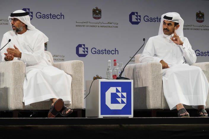 Qatar's Minister of State for Energy Affairs Saad Sherida al-Kaabi, right, listens to Emirati Energy and Infrastructure Minister Suhail al-Mazrouei, left, during the Gastech 2021 conference in Dubai, United Arab Emirates, Tuesday, Sept. 21, 2021. Energy officials from Qatar and Turkey, long-standing foes of the United Arab Emirates, descended on Dubai along with hundreds of other executives on Tuesday, flocking to the largest gas expo in the world and the industry's first in-person conference since the pandemic began. (AP Photo/Jon Gambrell)