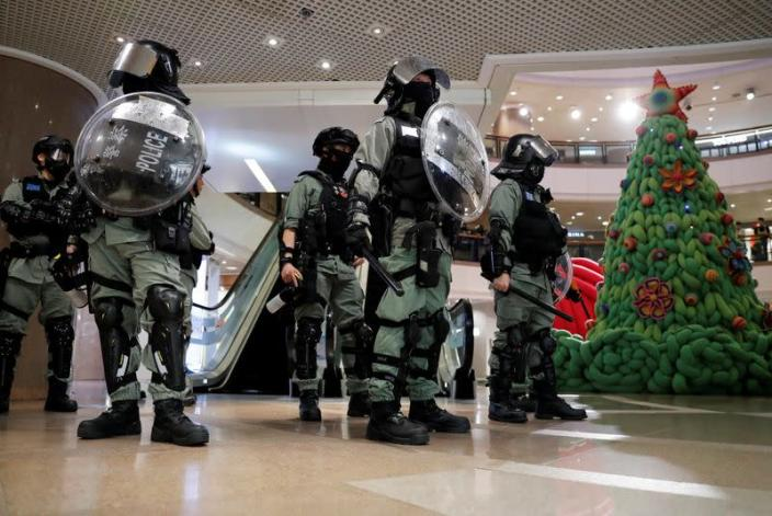Riot police stand guard next to a Christmas tree inside a shopping mall during an anti-government protest on Christmas Eve at Tsim Sha Tsui in Hong Kong
