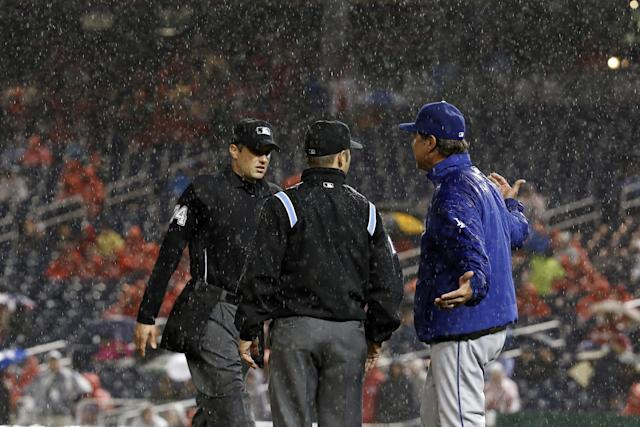 Umpire John Tumpane, left, and umpire Mark Wegner listen to Los Angeles Dodgers manager Don Mattingly (8) as he comes out during the fourth inning of a baseball game against the Washington Nationals at Nationals Park, Monday, May 5, 2014, in Washington. The game is rain delayed in the fourth inning. (AP Photo/Alex Brandon)