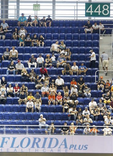 Baseball fans occupy a hal-empty section of Marlins Park stadium during the first inning of a baseball game between the Miami Marlins and the Houston Astros, Sunday, April 15, 2012, in Miami. (AP Photo/Wilfredo Lee)