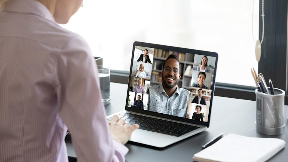 Close up of woman worker sit at desk talk speak on video call with multiracial colleagues or friends, female employee have online briefing with international team, engaged webcam conference at home
