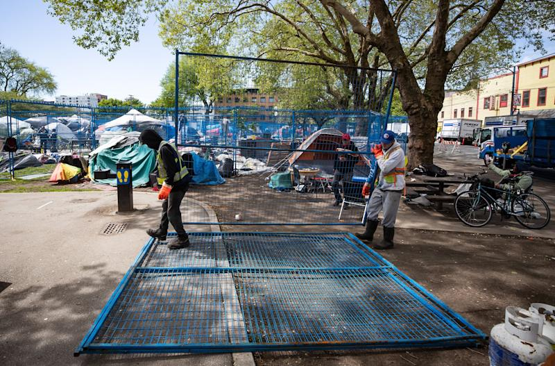 Workers deliver fencing to a homeless camp at Oppenheimer Park in the Downtown Eastside of Vancouver, on Wednesday, May 6, 2020. (Photo: Darryl Dyck/THE CANADIAN PRESS)