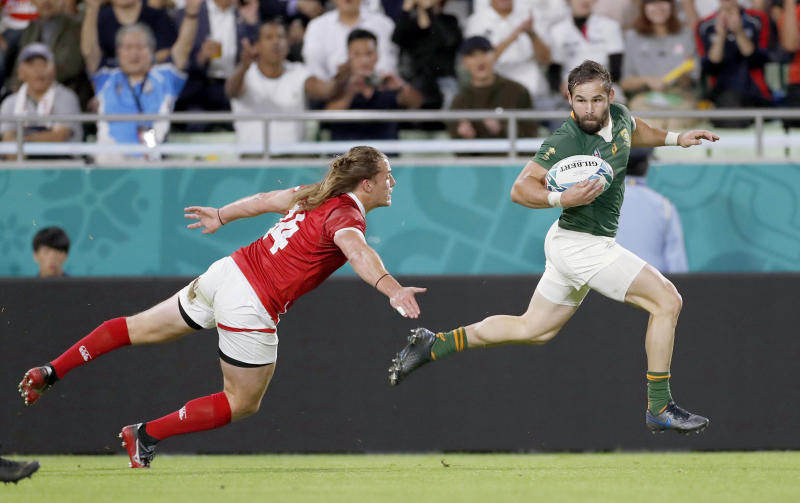 South Africa's Cobus Reinach runs clear of Canada's Jeff Hassler during the Rugby World Cup Pool B game at Kobe Misaki Stadium between South Africa and Canada in Kobe, Japan, Tuesday, Oct. 8, 2019. (Kyodo News via AP)