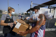 Los Angeles Unified School District food service worker Marisel Dominguez, left, distributes free school lunches and a weekend box to parent Ernesto Cortes on Friday, July 16, 2021, at the Liechty Middle School in Los Angeles. Flush with cash from an unexpected budget surplus, California is launching the nation's largest statewide universal free lunch program. When classrooms open for the fall term, every one of California's 6.2 million public school students will have the option to eat school meals for free, regardless of their family's income. (AP Photo/Damian Dovarganes)