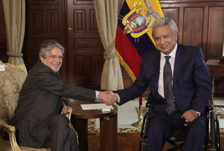 Ecuador's President Lenin Moreno, right, shakes hands with President-elect Guillermo Lasso during a meeting that is part of the presidential transition in Quito, Ecuador, Monday, April 19, 2021