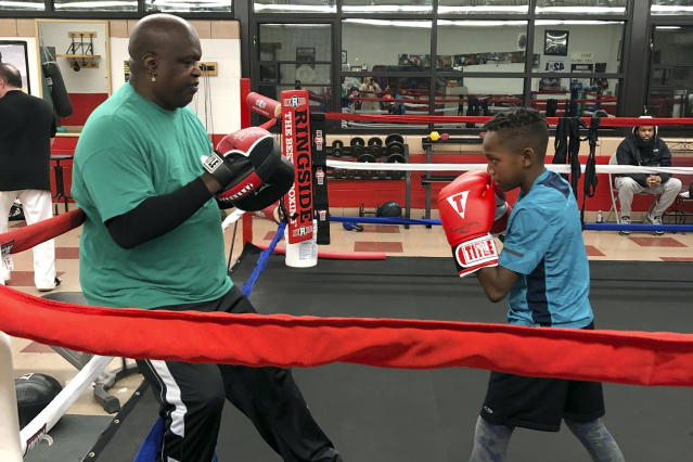 "In this Tuesday, Feb. 4, 2020 photo, James ""Buster"" Douglas, the former world heavyweight champion, works with a student at the Thompson Community Center in Columbus, Ohio, where he teaches youth boxing. In one of the more spectacular upsets in sports history, Douglas defeated Mike Tyson, the reigning world heavyweight champion on Feb. 11, 1990, in Tokyo. (AP Photo/Julie Carr Smyth)"