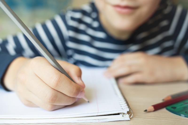 Kid writing in notebook and smiling. Close up.