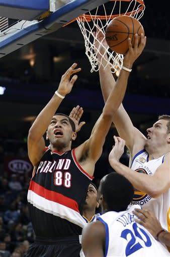 Portland Trail Blazers Nicolas Batum (88) drives to the basket against Golden State Warriors' David Lee and Ekpe Udoh (20) during the first half of an NBA basketball game in Oakland, Calif., Wednesday, Feb. 15, 2012. (AP Photo/Tony Avelar)