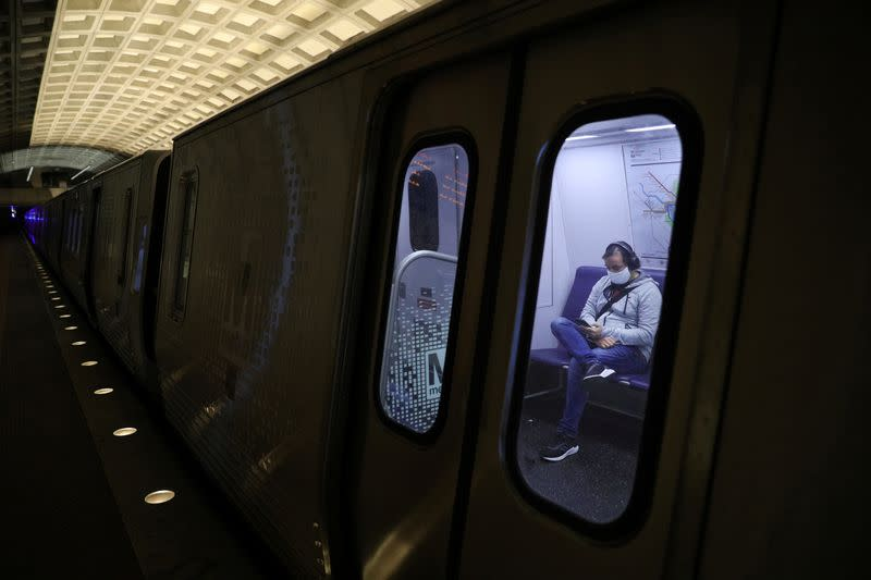 A passenger wearing a protective face mask uses a cell phone, following the WMATA Metro rule stating riders must wear protective face masks amid the coronavirus disease (COVID-19) outbreak, in Washington