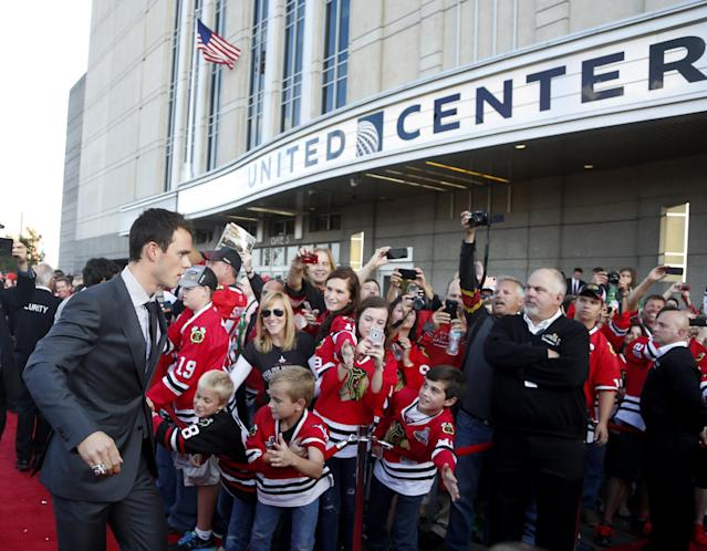 Chicago Blackhawks' center Jonathan Toews walks the red carpet outside the United Center as the team arrives for their season-opening NHL hockey game against the Washington Capitals Tuesday, Oct. 1, 2013, in Chicago. (AP Photo/Charles Rex Arbogast)