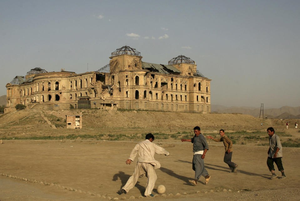 FILE -- In this July 1, 2008 file photo, Afghans play football in front of the destroyed Darul Aman Palace in the western part of Kabul, Afghanistan. The Taliban fighters who rolled into Afghanistan's capital and other cities in recent days appear awestruck by the towering apartment blocks, modern office buildings and shopping malls. When the Taliban last seized power, in 1996, the country had been ravaged by civil war and the capital was in ruins. (AP Photo/Farzana Wahidy, File)