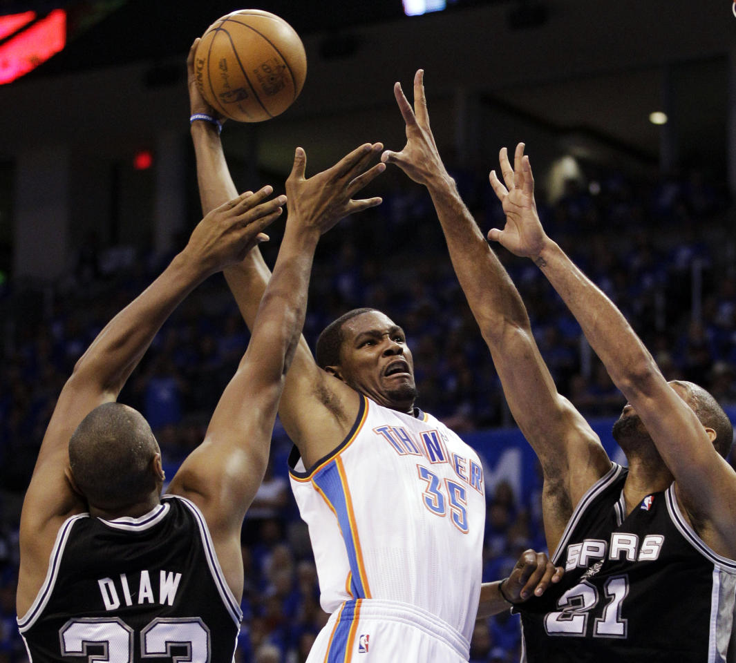 Oklahoma City Thunder small forward Kevin Durant (35) shoots against San Antonio Spurs' Boris Diaw (33), of France ,and Tim Duncan (21) during the first half of Game 3 in their NBA basketball Western Conference finals playoff series, Thursday, May 31, 2012, in Oklahoma City. (AP Photo/Sue Ogrocki)