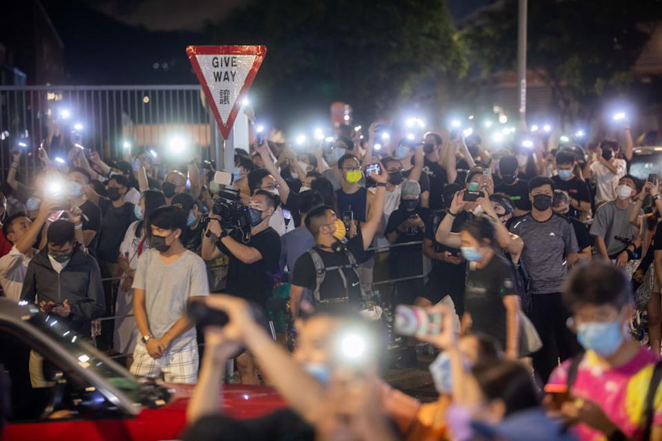 Supporters holding up mobile phone torches at the headquarters of the Apple Daily newspaper.