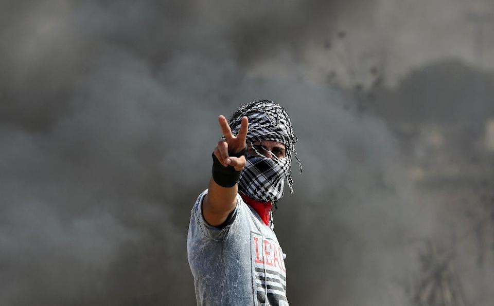 A Palestinian protester flashes the sign for victory during clashes with Israeli security forces near the Nahal Oz border crossing with Israel, east of Gaza City on October 10, 2015 (AFP Photo/Mahmud Hams)