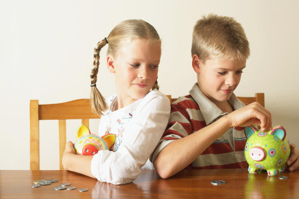 Pictured: Two blonde children with piggy banks. Image: Getty