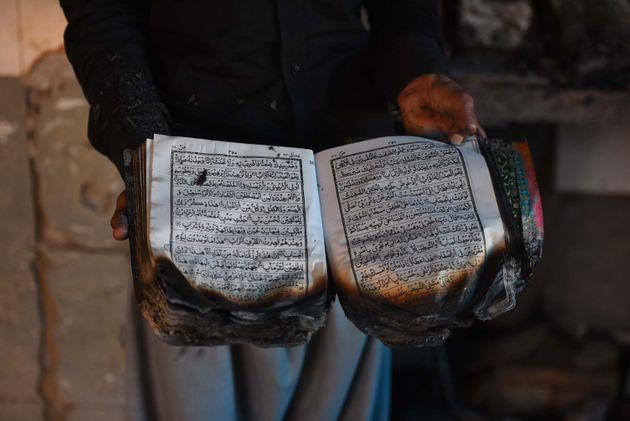 A man holds the holy Quran that was burnt along with the mosque at Mustafabad, on February 26, 2020 in New Delhi, India.
