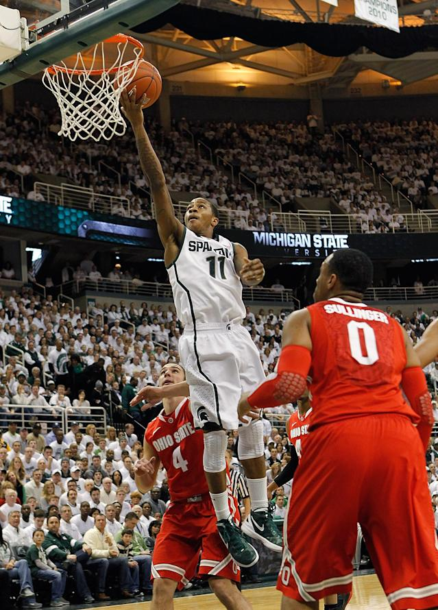 EAST LANSING, MI - MARCH 04: Keith Appling #11 of the Michigan State Spartans scores over Aaron Craft #4 and Jared Sullinger #0 of the Ohio State University during the first quarter of the game at Breslin Center on March 4, 2012 in East Lansing, Michigan. (Photo by Leon Halip/Getty Images)