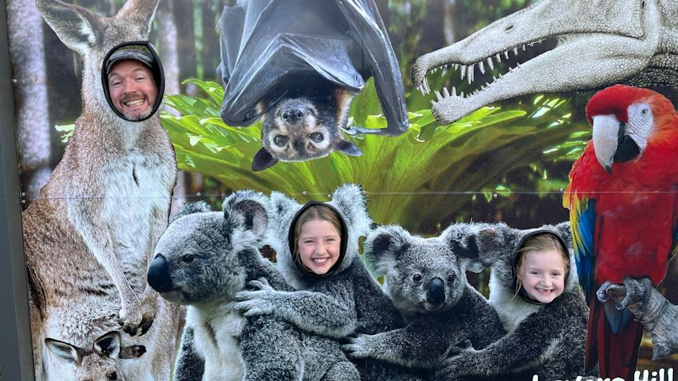 Owain Emslie and his two daughters pose as koalas and kangaroos behind a cut out picture frame.