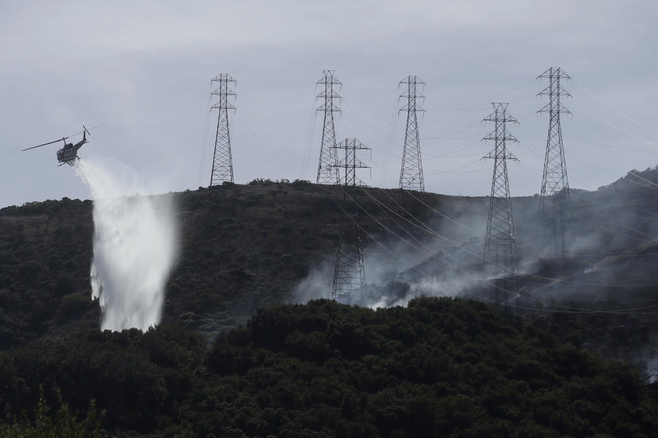 FILE - In this Oct. 10, 2019, file photo, a helicopter drops water near power lines and electrical towers while working at a fire on San Bruno Mountain near Brisbane, Calif. A federal judge overseeing Pacific Gas & Electric's criminal probation is considering requiring the utility to be more aggressive about turning off its electricity lines. The plan outlined Tuesday, March 23, 2021, would add more power shut-offs near tall trees and would at least double the number of power outages in six Northern California counties. (AP Photo/Jeff Chiu, File)