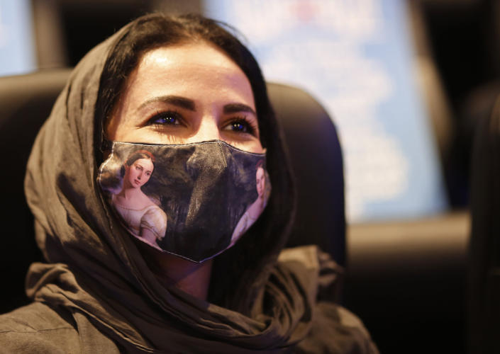 In this June 26, 2020 photo, a Saudi woman wears a colored face mask to help curb the spread of the coronavirus, at VOX Cinema hall in Jiddah, Saudi Arabia. In the two decades since Sept. 11, 2001, Saudi Arabia has confronted al-Qaida on its own soil, revamped its textbooks, worked to curb terror financing and partnered with the United States to counter terrorism. (AP Photo/Amr Nabil)