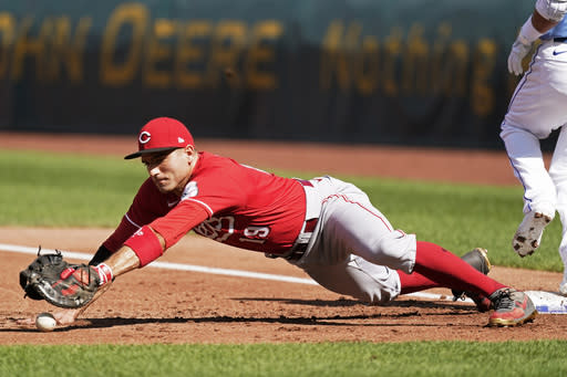 Cincinnati Reds first baseman Joey Votto tries to get control of the ball after Kansas City Royals' Whit Merrifield reached first on a fielding error during the first inning of game one of a baseball double-header Wednesday, Aug. 19, 2020, in Kansas City, Mo. (AP Photo/Charlie Riedel)