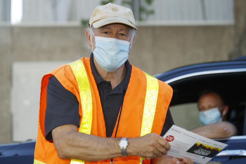 Election judge Michael Michalek wears a face mask while collecting ballots as voters drop them off at a drive-thru location outside the Denver Election Commission building Tuesday, June 30, 2020, in downtown Denver. (AP Photo/David Zalubowski)