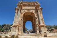 One of the few visitors to the ancient Roman city of Leptis Magna in Libya looks at the Arch of Septimius Severus (AFP/Mahmud TURKIA)
