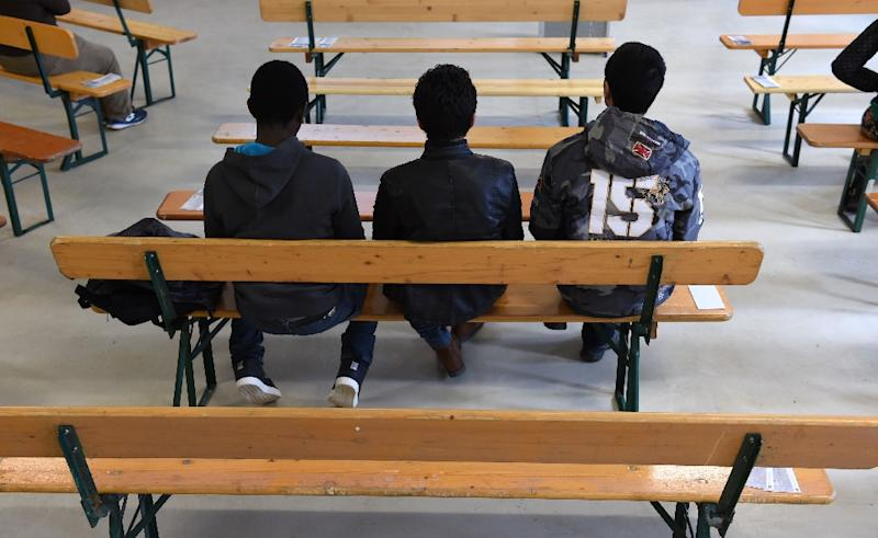 """Migrants wait for the start of the rights education lessons for refugees and asylum seekers in a hall of the """"Bayernkaserne"""" in Munich, southern Germany on February 24, 2016"""