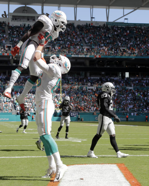 Miami Dolphins tight end Mike Gesicki (86) hoists up wide receiver Jakeem Grant (19) after Grant scored a touch down during the second half of an NFL football game against the Oakland Raiders, Sunday, Sept. 23, 2018 in Miami Gardens, Fla. (AP Photo/Lynne Sladky)