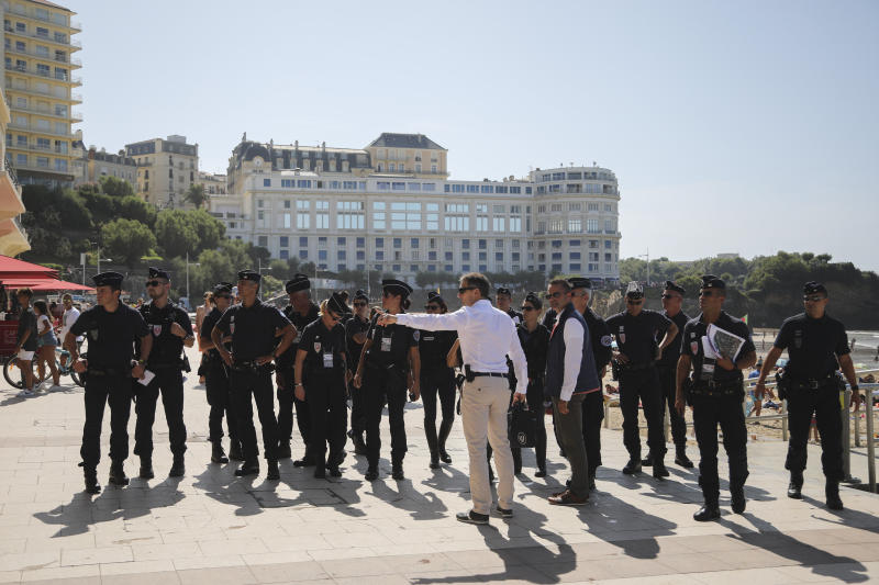 French police officers get instructions in front of the Le Bellevue at the beach promenade ahead of the upcoming G7 Summit, in Biarritz, France, Thursday, Aug. 22, 2019. The G7 Summit will host the heads of countries with advanced economies from United States, Britain, Canada, Germany, Italy, Japan and France and will be held in Biarritz between the 24th and 26th of August. (AP Photo/Markus Schreiber)