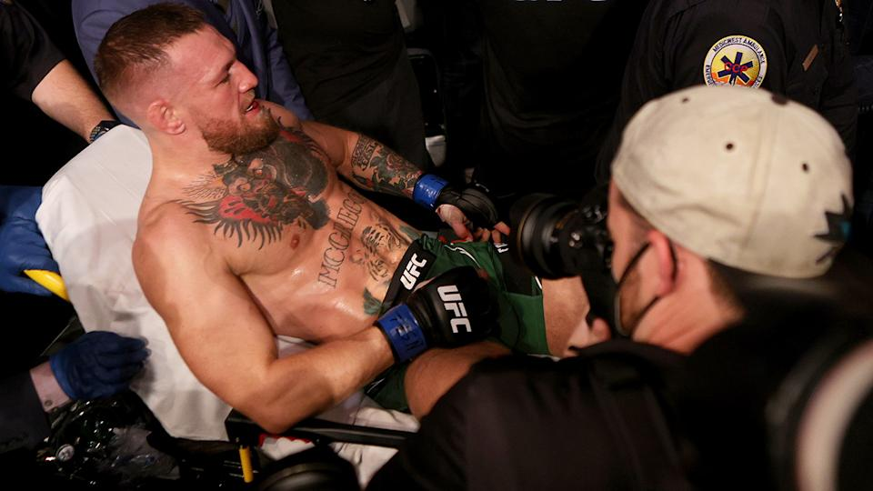 Conor McGregor was carried out of the arena on a stretcher after breaking his ankle in the first round of his lightweight bout against Dustin Poirier at UFC 264. (Photo by Stacy Revere/Getty Images)