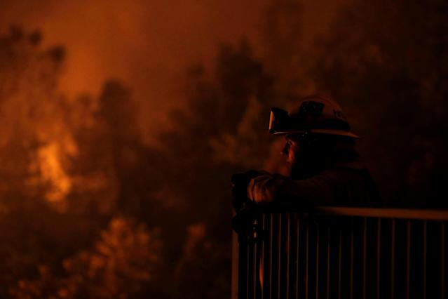 <p>Cal Fire firefighter Zach Hallums is seen as fire burns in a canyon below homes as crews battle the Carr Fire, west of Redding, Calif., July 27, 2018. (Photo: Fred Greaves/Reuters) </p>