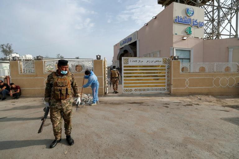Iraqi policemen stand at the gate of Baghdad's Ibn al-Khatib hospital, which was ravaged by a fire that killed at least 82