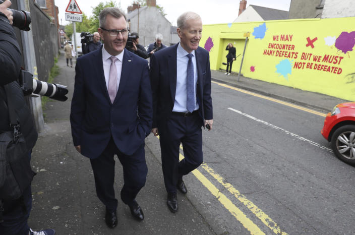 Northern Ireland lawmaker Jeffrey Donaldson, left, leaves the Democratic Unionist Party (DUP) headquarters in Belfast, Northern Ireland, after voting in the party's leadership election, Friday May 14, 2021. Northern Ireland's largest British unionist party is choosing a new leader Friday, in a contest between Northern Ireland lawmakers Edwin Poots and Jeffrey Donaldson, with only 36 eligible voters and the result due late Friday afternoon. (Brian Lawless/PA via AP)