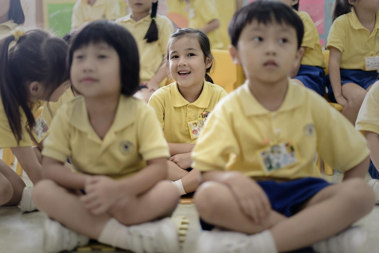 Maia (center) sits at her school in Hong Kong on June 17, 2013.