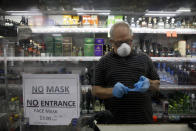Liquor store worker Mario Valle puts on protective gloves behind a sign requiring face masks in the Vermont Square neighborhood of Los Angeles, Thursday, May 21, 2020. While most of California is welcoming a slight return toward normal this holiday weekend, Los Angeles will not be joining the party. The nation's largest county is not planning to reopen more widely until the next summer holiday, July 4th, because of a disproportionately large share of the state's coronavirus cases and deaths that have hampered the county's ability to rebound and meet strict criteria to get more people back to work.(AP Photo/Jae C. Hong)