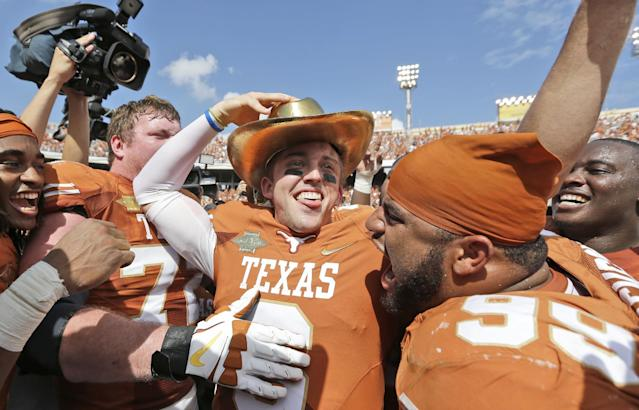 Texas quarterback Case McCoy (6) dons the golden hat trophy as he celebrates with teammate including Desomond Jackson (99) after their 36-20 win over Oklahoma in an NCAA college football game at the Cotton Bowl Saturday, Oct. 12, 2013, in Dallas. (AP Photo/LM Otero)