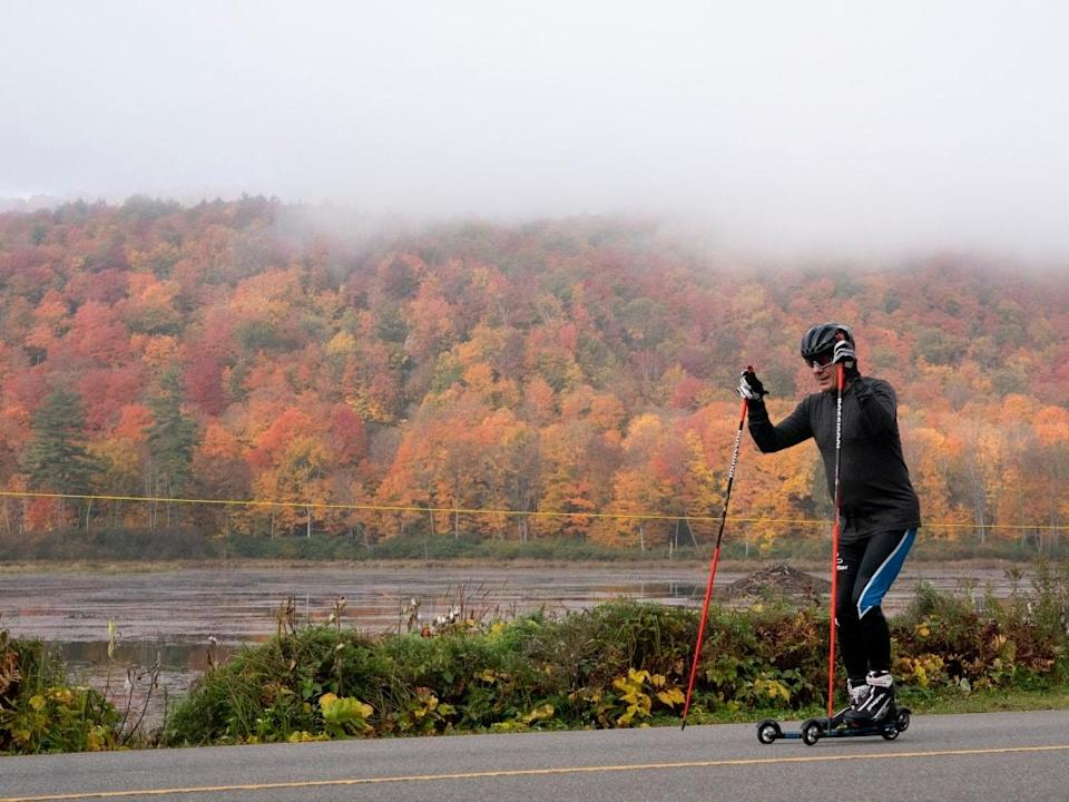 The fog lifts as a man roller-skis through Gatineau Park, Tuesday, Oct. 12, 2021 in Chelsea, Que. (Adrian Wyld/The Canadian Press - image credit)