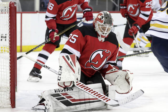 New Jersey Devils goaltender Cory Schneider blocks a shot from Buffalo Sabres left wing Jeff Skinner, not visible, during the third period of an NHL hockey game, Monday, March 25, 2019, in Newark, N.J. The Devils won 3-1. (AP Photo/Julio Cortez)