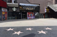 """A video marquee in the empty forecourt of Madame Tussauds Hollywood plays a """"Stay Strong Hollywood!"""" message as stay-at-home orders continue in California due to the coronavirus, Tuesday, March 31, 2020, in Los Angeles. (AP Photo/Chris Pizzello)"""