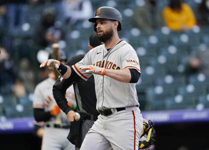 San Francisco Giants' Brandon Belt crosses home plate after hitting a two-run home run against the Colorado Rockies in the first inning of game two of a baseball doubleheader Tuesday, May 4, 2021, in Denver. (AP Photo/David Zalubowski)