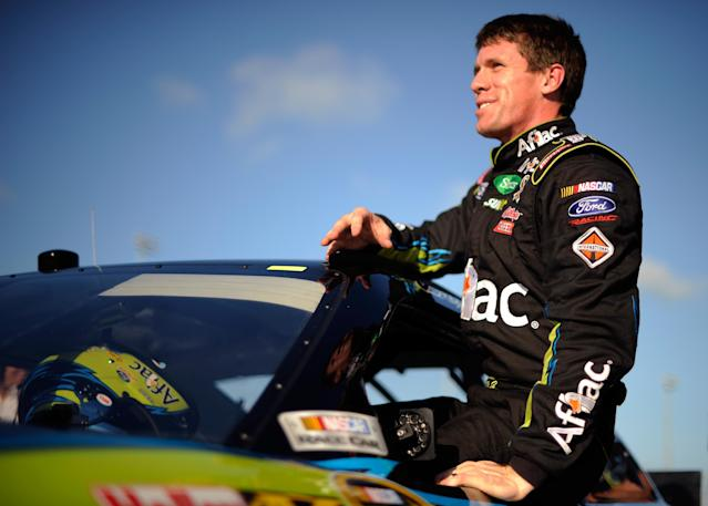 HOMESTEAD, FL - NOVEMBER 19: Carl Edwards, driver of the #99 Aflac Ford, climbs out of his car after qualifying for pole position in the NASCAR Sprint Cup Series Ford 400 at Homestead-Miami Speedway on November 19, 2011 in Homestead, Florida. (Photo by Jared C. Tilton/Getty Images)