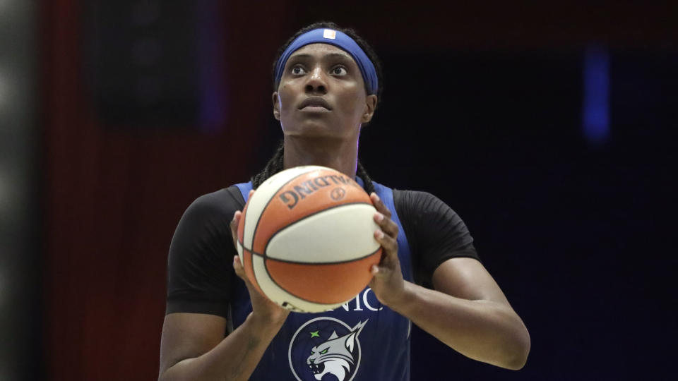 Minnesota Lynx center Sylvia Fowles holding the ball ready to shoot with a dark background.